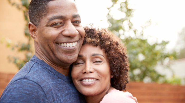 Featured | Happy middle aged black couple embracing smile to camera | More Sex Can Prevent Heart Attacks, According To Science